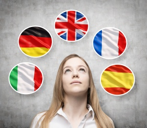 Beautiful lady is surrounded by bubbles with european countries' flags (Italian, German, Great Britain, French, Spanish). Learning of foreign languages concept. Concrete background.