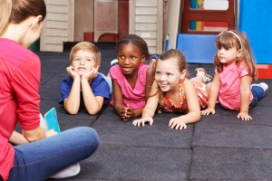 Kindergärtnerin liest Kindern eine Geschichte aus einem Buch vor im Kindergarten